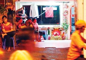 หญิงชาวเขมรนั่งรอลูกค้าหน้าร้านคาราโอเกะในกรุง พนมเปญ สหประชาชาติวิตกปัญหาแรงงานเขมรตกงานในภาวะวิกฤติเศรษฐกิจจะทำให้หญิงชาว เขมรที่ตกงานหันหน้ามาทำงานในสถานบันเทิงหรือขายบริการทางเพศมากขึ้น